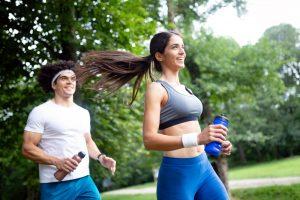 Homem e mulher realizam atividade física em parque